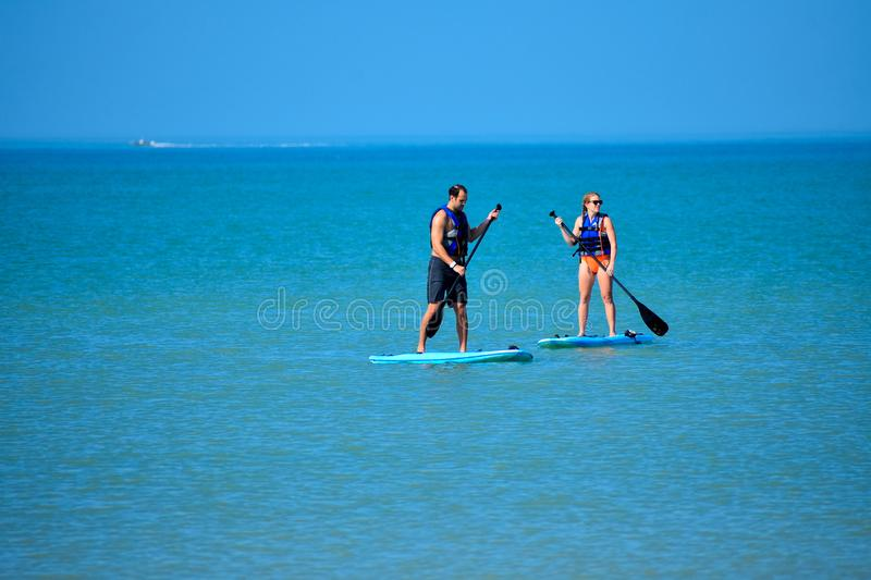 Couple enjoying stand up paddle board on blue sea background 1 stock image