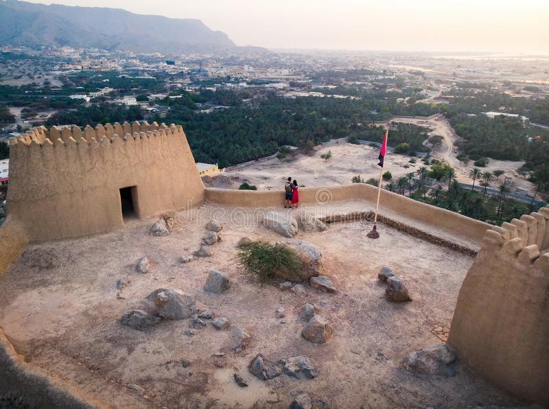 Couple enjoying sunset view from Dhayah fort in the UAE. Couple enjoying sunset view from Dhayah fort in Ras Khaimah emirate in UAE aerial fortress desert stock photography