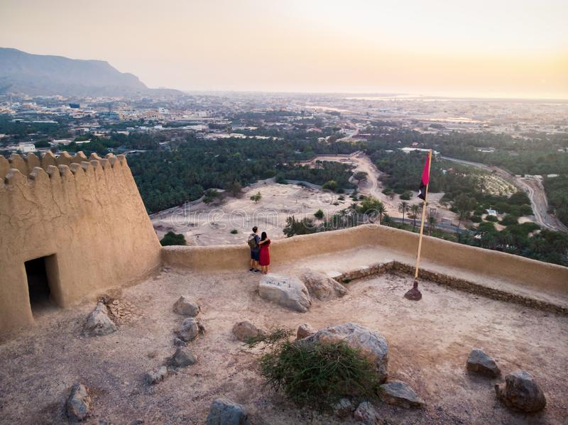 Couple enjoying sunset view from Dhayah fort in the UAE. Couple enjoying sunset view from Dhayah fort in Ras Khaimah emirate in UAE aerial fortress desert royalty free stock images