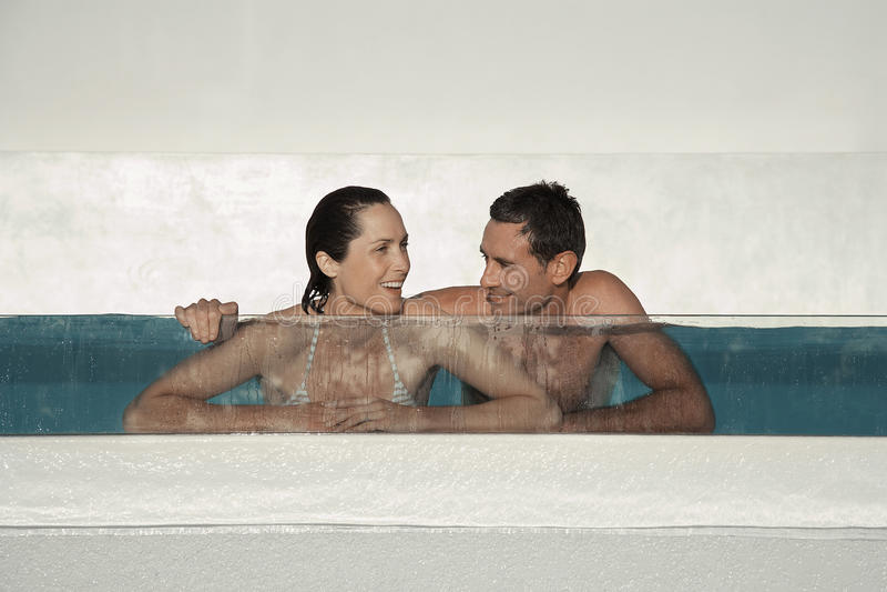Couple Enjoying In Swimming Pool. Happy couple enjoying in swimming pool at resort stock photo
