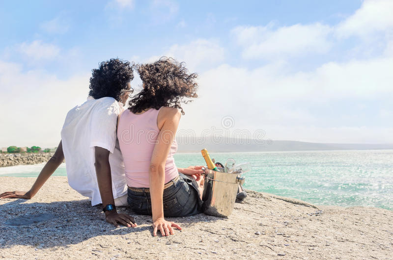 Couple enjoying themselves by the sea with champagne sparking wi stock photo