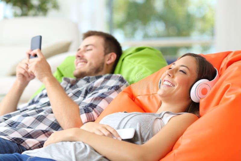 Couple enjoying using phone and listening to music stock images