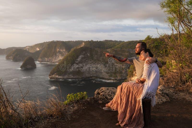 Couple enjoying view from Banah Cliff of Nusa Penida island, Indonesia stock image