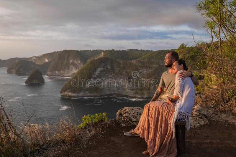 Couple enjoying view from Banah Cliff of Nusa Penida island, Indonesia royalty free stock image