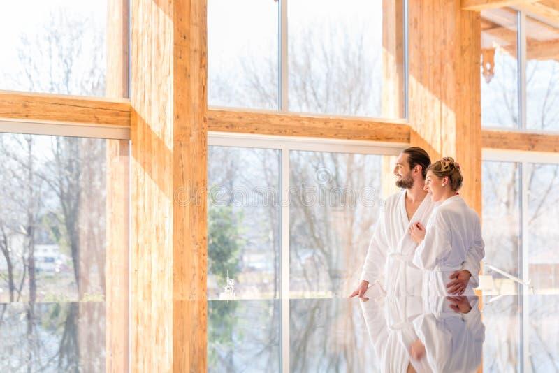 Couple enjoying view on wellness spa pool. Couple on pool looking relaxed throw window of wellness spa wearing bath robe stock photo
