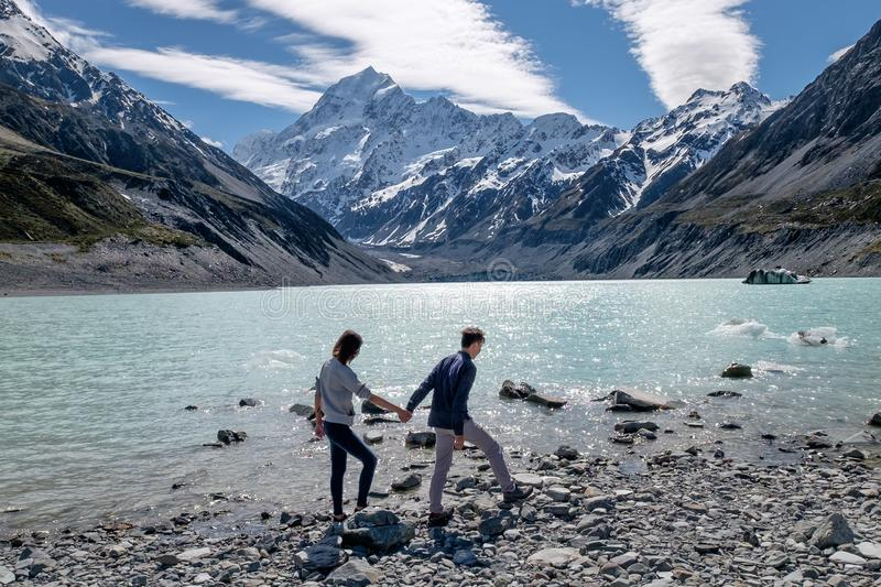 Loving image of couple holding hands at Mount Cook, New Zealand stock image