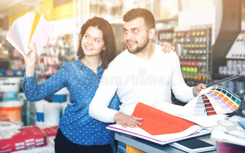 Couple examining color scheme variants. Cheerful young couple examining color scheme variants in paint supplies supermarket royalty free stock photo