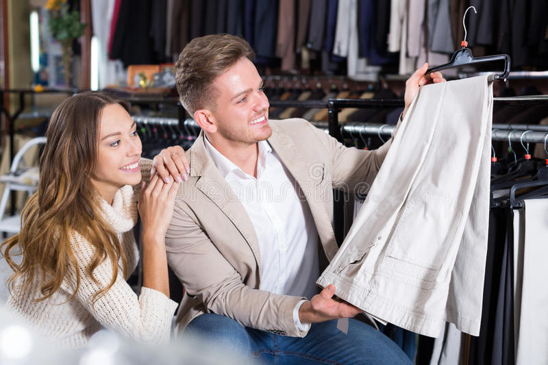 Download Couple Examining Various Trousers Stock Photo - Image: 83702062