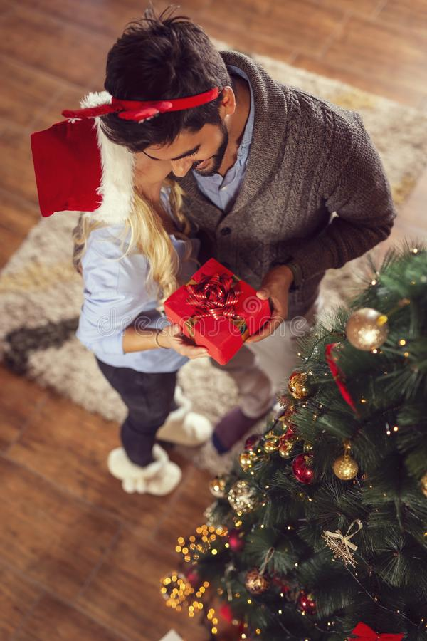 Couple exchanging Christmas gifts. High angle view of a beautiful couple in love, wearing santa hats, standing next to a nice decorated Christmas tree royalty free stock photo