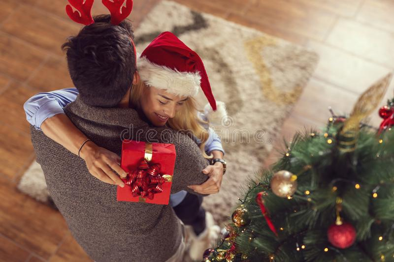 Couple exchanging Christmas presents. High angle view of a beautiful couple in love, wearing santa hats, standing next to a nice decorated Christmas tree royalty free stock photos