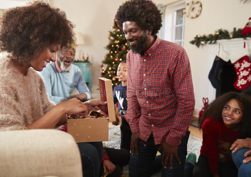 Couple Exchanging Gifts As Multi Generation Family Celebrate Christmas At Home Together stock image