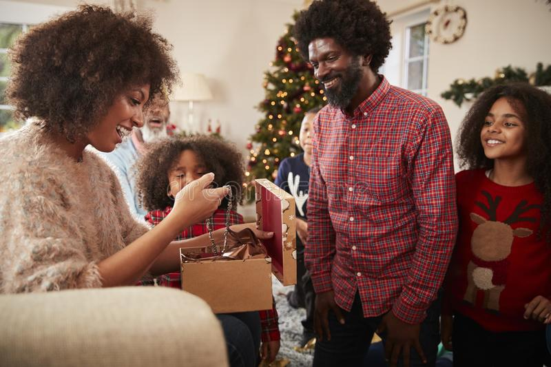 Couple Exchanging Gifts As Multi Generation Family Celebrate Christmas At Home Together stock photo