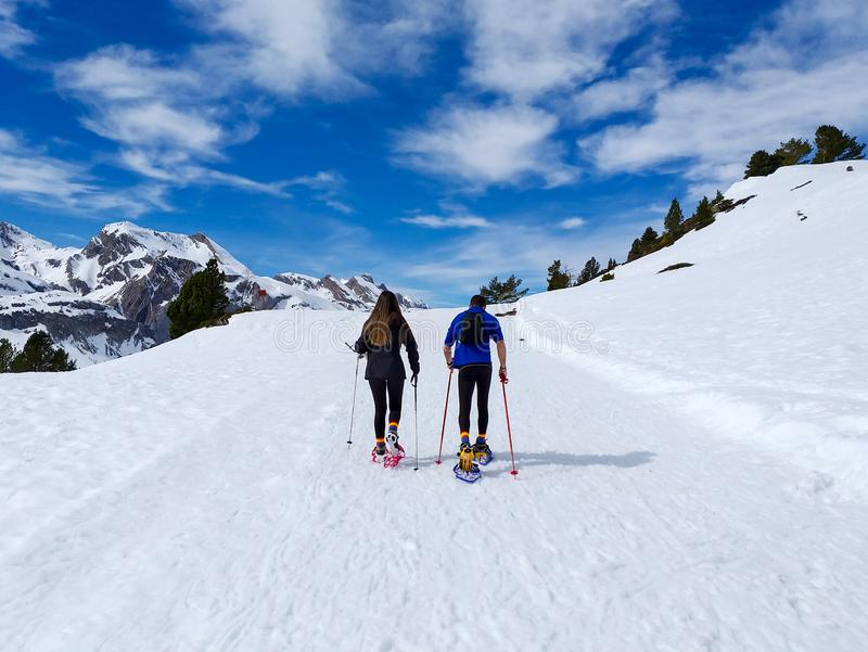 couple of excursionists walking on snowshoes and stick poles on the white snow of the winter of a path of a snowy mountain royalty free stock images
