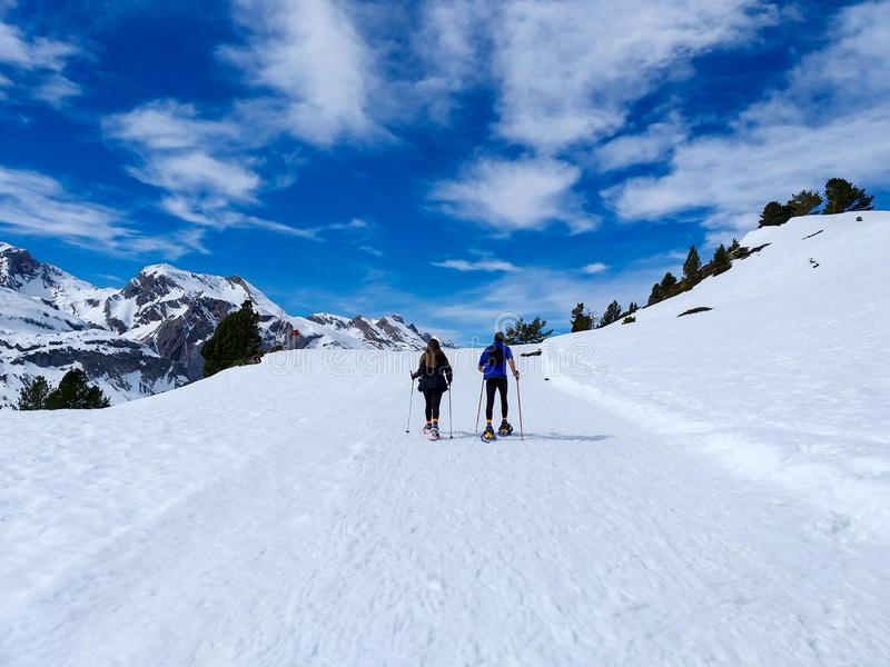 couple of excursionists walking on snowshoes and stick poles on the white snow of the winter of a path of a snowy mountain stock images