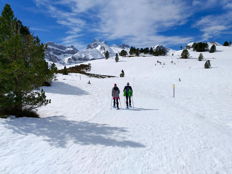 couple of excursionists walking on snowshoes and stick poles on the white snow of the winter of a path of a snowy mountain royalty free stock photos