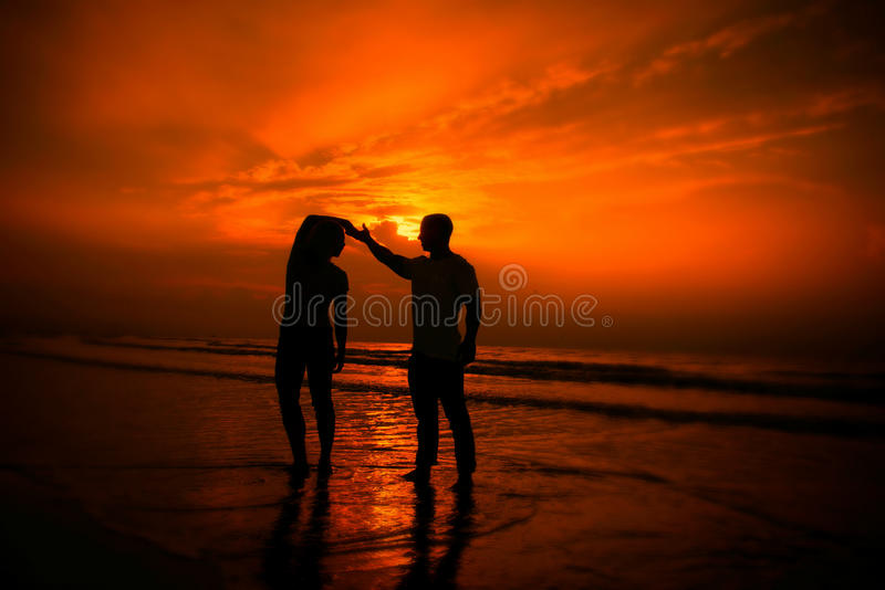 Couple exercising on the beach. Silhouetted couple exercising on the beach with a bright orange sunset background royalty free stock images