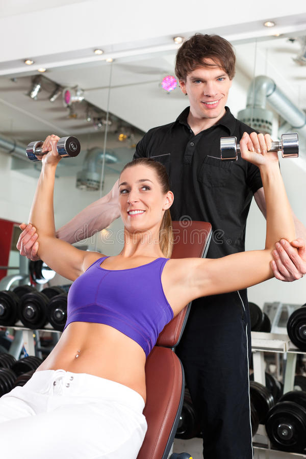 Couple exercising in gym with weights