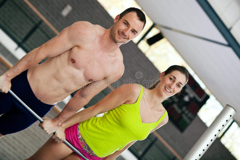 Couple exercising on high bar