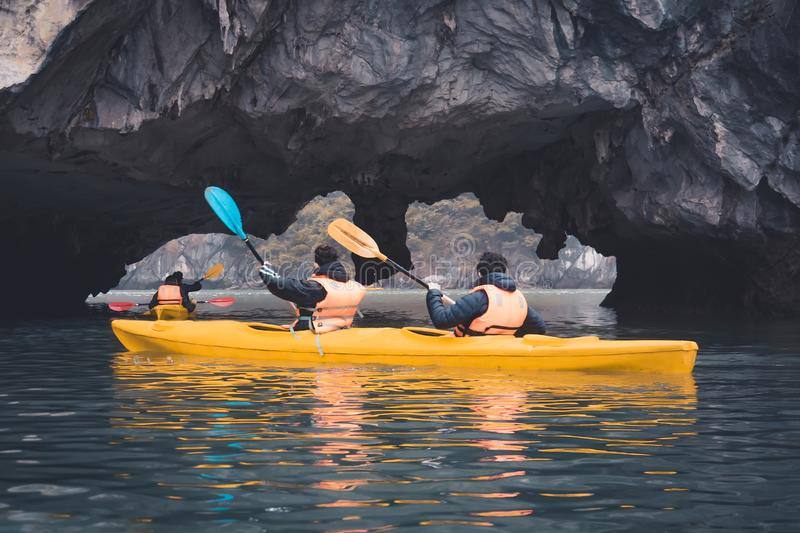 Couple exploring cave on kayak and taking photograps in the boat. Ha Long Bay, Vietnam, Cat Ba Island stock photography