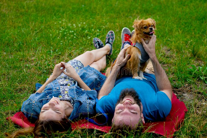 Young couple enjoying with a dog in a city park. stock photos