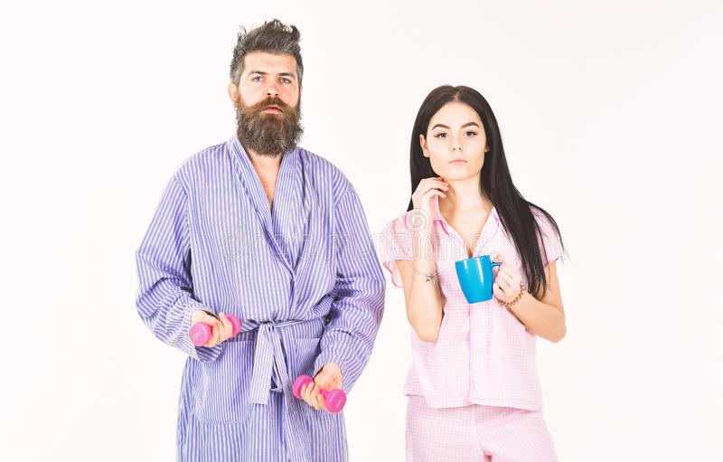 Couple, family offers alternative energy source. Couple in love in pajama, bathrobe stand isolated on white background. Man with dumbbell, girl with coffee cup royalty free stock photo