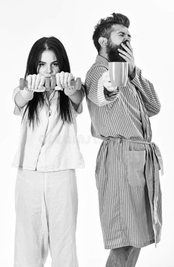Couple, family offers alternative energy source. Couple in love in pajama, bathrobe stand isolated on white background. Girl with dumbbell, men with coffee cup stock photo