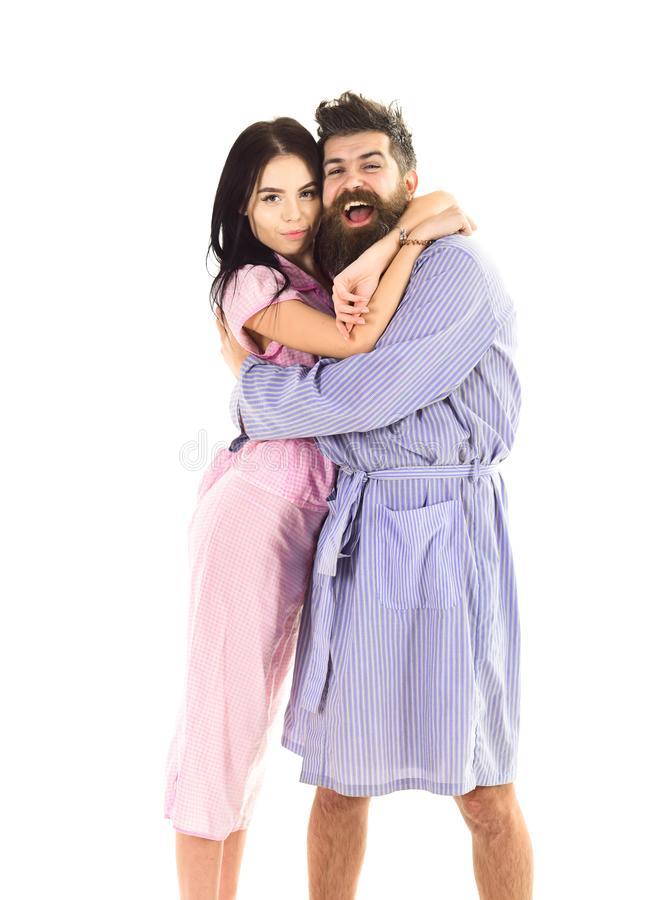 Couple, family on smiling faces in clothes for sleep looks happy in morning. Couple in love hugging in pajama, bathrobe. Perfect morning concept. Couple stock photography