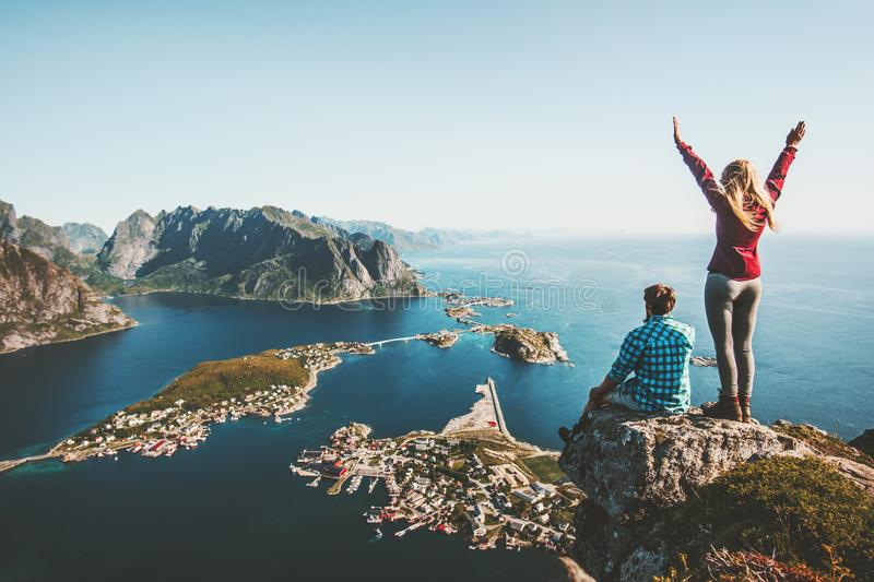 Couple family traveling together on cliff edge in Norway. Man and woman lifestyle concept summer vacations outdoor aerial view Lofoten islands Reinebringen stock photography
