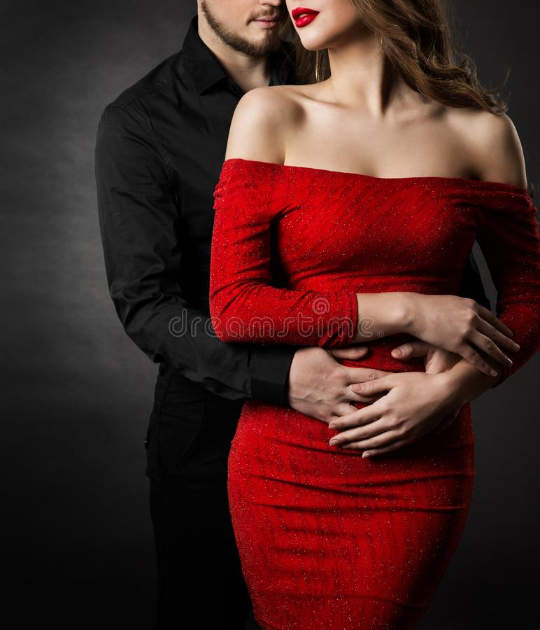 Couple Fashion Beauty, Woman in Red Dress and Embracing Man in Love royalty free stock image