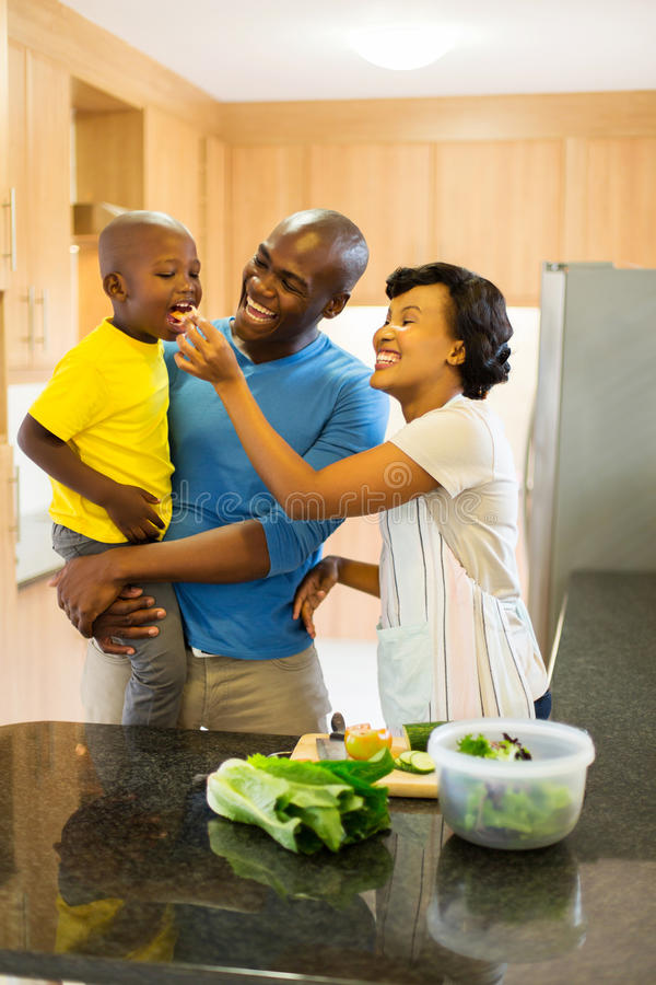Couple feeding son vegetable. Cheerful young african couple feeding son vegetable royalty free stock images