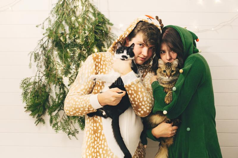 Couple in festive pajamas hugging their cats and having fun at modern christmas tree with lights. Celebrating Christmas or New royalty free stock photos