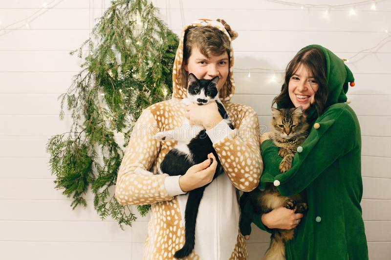 Couple in festive pajamas hugging their cats and having fun at modern christmas tree with lights. Celebrating Christmas or New stock photos
