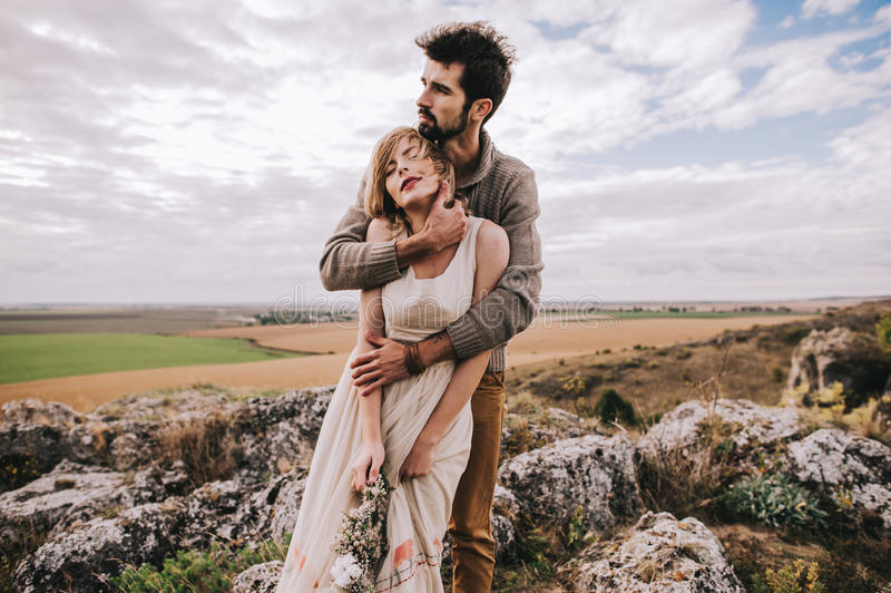 Couple in the field near the mountains royalty free stock image