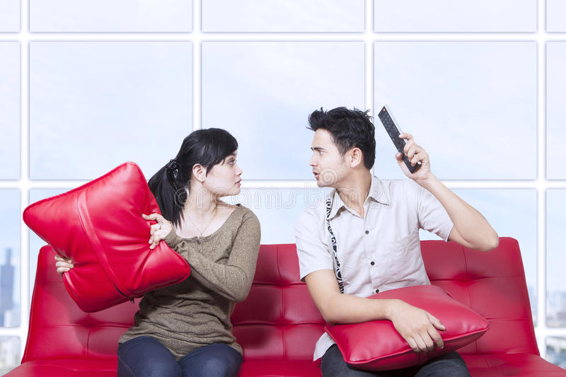 Couple fight on red sofa - indoor. Couple fight on red sofa in apartment stock images