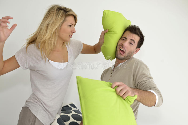 Couple fighting. Angry couple throwing pillows at each other stock photos