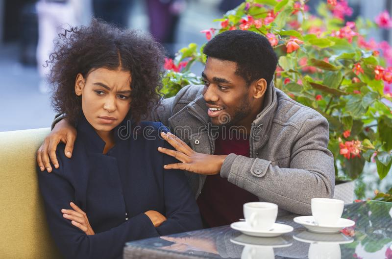Cheerful black guy trying to cheer up his angry girlfriend royalty free stock photo