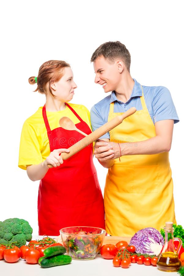 couple fighting with kitchen utensils while cooking salad on white stock photo