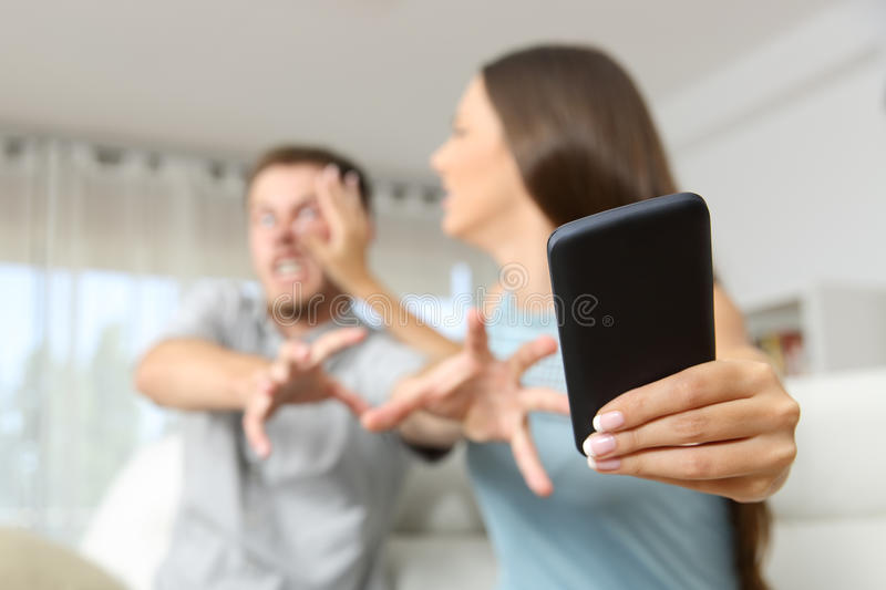 Couple fighting for a mobile phone. Angry couple or marriage fighting for a mobile phone at home royalty free stock photography