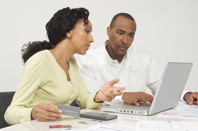 Couple Figuring Out Finances. An African American couple figuring out finances on laptop stock photography