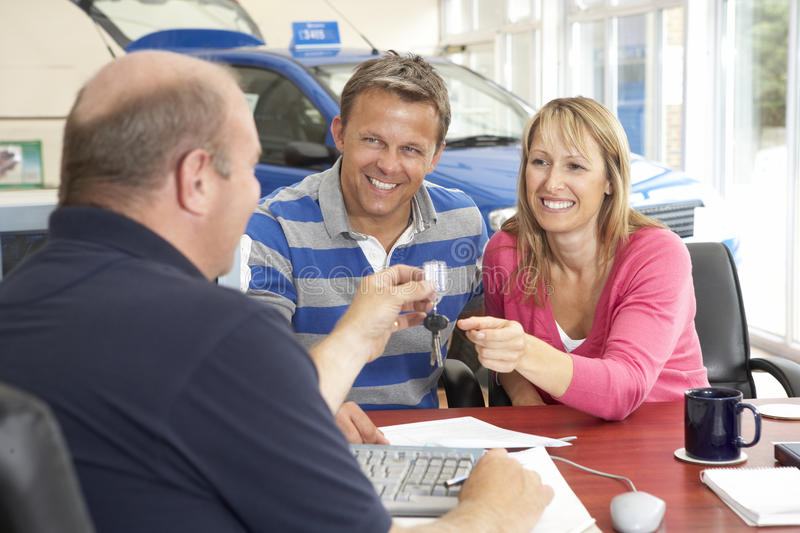Couple filling in paperwork in car showroom stock photography