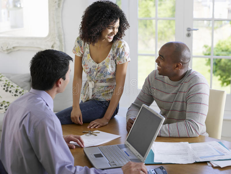 Couple With Financial Advisor At Table stock image