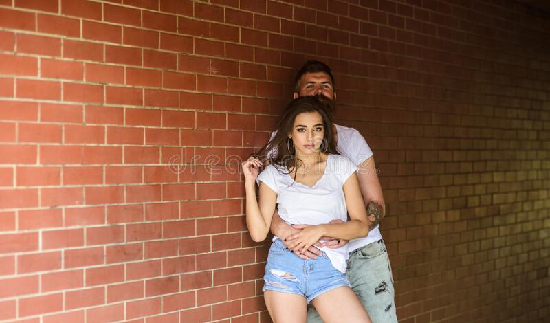 Couple find place to be alone. Couple in love hugs brick wall background. He will never let her go. Girl and hipster stock photography