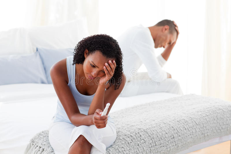 Couple finding out results of a pregnancy test. Upset couple finding out results of a pregnancy test in the bedroom stock images