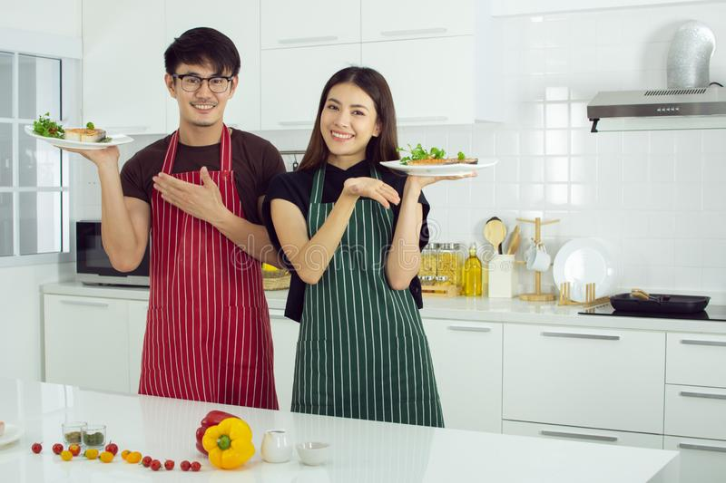 A couple finish cooking and they have large smiles stock image