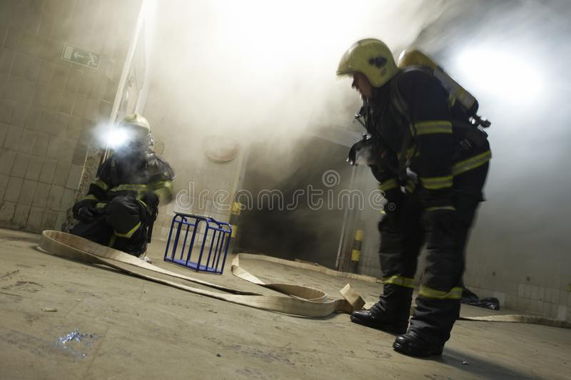 The couple of firemen fighting with the fire