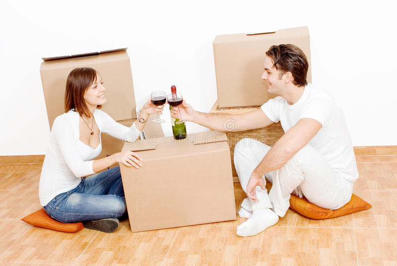 Couple first new home. Young couple toasting their first new home and moving in royalty free stock images
