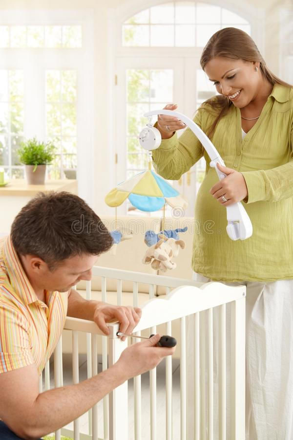 Download Couple Fixing Baby Bed Together Stock Photo - Image: 27720652
