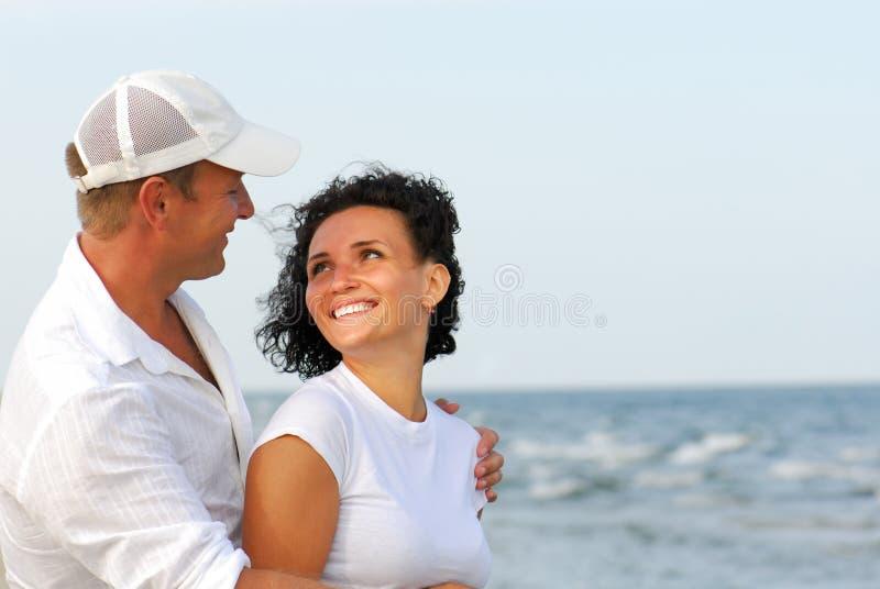 Couple flirting on beach. Heterosexual couple flirting on beach royalty free stock photography