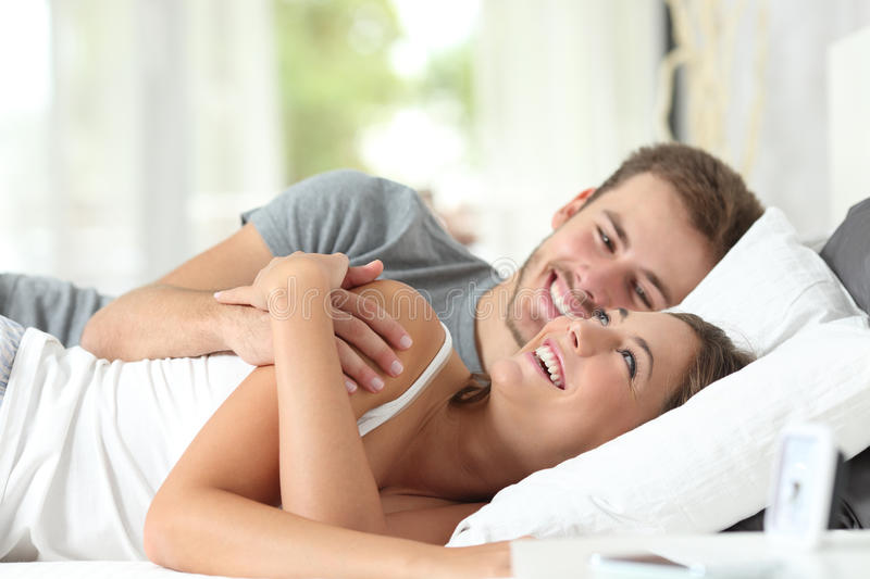 Couple flirting on a bed at home. Happy couple flirting in the morning on the bed at home stock image