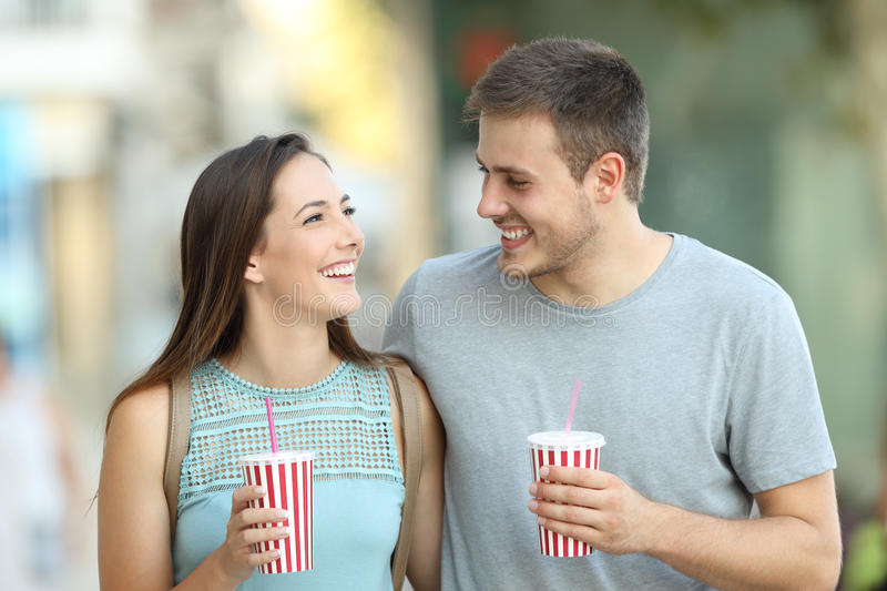 Couple flirting and holding takeaway refreshments. Front view portrait of a happy couple flirting and holding takeaway refreshments in the street royalty free stock photography